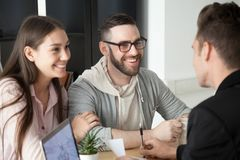 Excited smiling millennial couple discussing mortgage loan inves