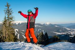 Snowboarder resting on top of the mountain Stock Photo