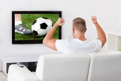 Excited soccer fan watching a game Stock Photography