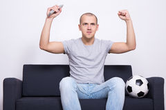Excited soccer fan watching game on television Stock Photos