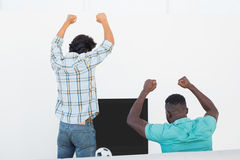 Excited soccer fans cheering while watching tv. Rear view of two excited soccer fans cheering while watching tv Royalty Free Stock Photography