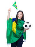 Excited soccer fans holding Brazil flag and football Stock Photo