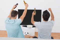 Excited soccer fans watching tv Stock Images