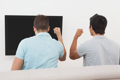 Excited soccer fans watching tv. Rear view of two excited soccer fans watching tv Royalty Free Stock Photos