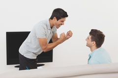 Excited soccer fans watching tv. Side view of two excited soccer fans watching tv Royalty Free Stock Photography