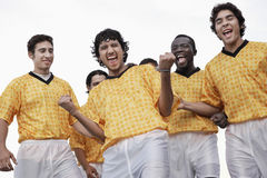 Excited Soccer Players Celebrating Victory Against Sky Royalty Free Stock Image
