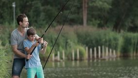 Excited son and father caught fish on bait in pond stock footage