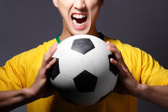 Excited sport man shouting and holding soccer. Excited young sport man shouting and holding soccer isolated on gray background Royalty Free Stock Photos
