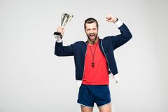 Excited sportive coach screaming and holding trophy cup,. Isolated on white stock image