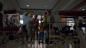 Excited sportive family in the gym. Slow motion of happy big family giving high-fives and showing thumbs-up after training in the gym. Child, parents and stock footage