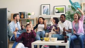 Excited sports fans enjoying game on TV laughing and doing high-five in flat. Excited sports fans men and women are enjoying game on TV laughing and doing high stock video