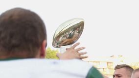 Excited sports team jumping with trophy in hands, celebrating victory together. Stock footage stock video