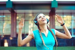 Excited sportswoman in headphones outdoors royalty free stock image