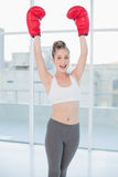Excited sporty blonde wearing red boxing gloves cheering Stock Images