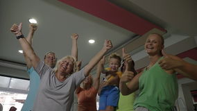 Excited sporty family with thumbs-up in the gym. Slow motion of parents, little son and grandparents showing thumbs-ups in the gym. Big family is happy to be in stock footage