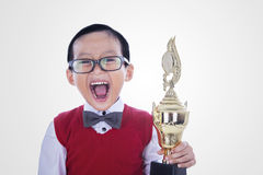 Excited student boy holding trophy - isolated. Excited student boy is holding trophy shouting for joy, isolated on white Stock Photo