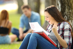 Excited student checking an approved exam. Sitting on the grass in a park with unfocused people in the background Royalty Free Stock Photo