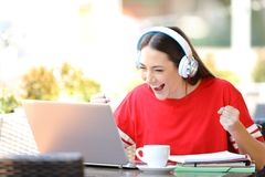 Excited student e-learning in a coffee shop. Excited student e-learning with a laptop and headphones finds offers in a coffee shop terrace stock photo