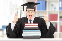 Excited student giving thumbs up behind stack of books. Excited college graduate giving thumbs up seated at table behind a stack of books, indoors Stock Photos