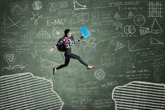 Excited student jumping on gap. Female student jumping in classroom through gap on the blackboard Royalty Free Stock Image