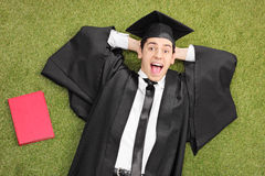 Excited student lying on green grass. An excited student in graduation gown, lying on green grass with a book next to him and looking at the camera Stock Photo