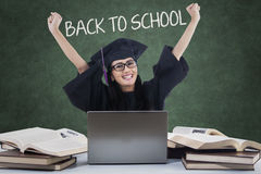 Excited student with mortarboard back to school. Portrait of excited female high school student back to school and raise hands while wearing mortarboard in the Stock Photography