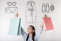 Excited student putting her hands up while doing shopping Royalty Free Stock Photography