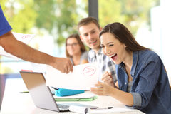 Excited student receiving an approved exam. From the teacher in a classroom stock photos