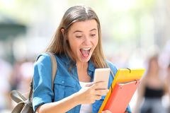Excited student receiving good online news. In the street stock photo