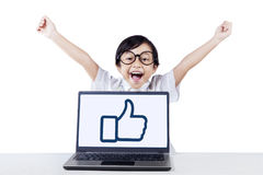 Excited student with thumb up icon isolated. Portrait of cheerful female student celebrating her victory while raise hands with thumb up icon on the laptop Stock Photography