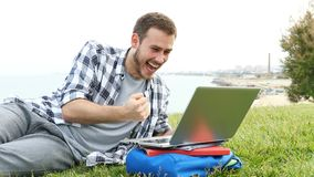 Excited student using a laptop on the grass. Excited student using a laptop checking good news lying on the grass stock video