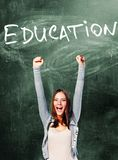 Excited student woman. Is standing with chalk board behind her Stock Photography
