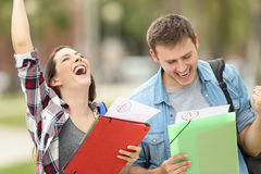 Excited students with approved exams. Two excited students with approved exams in the street stock image