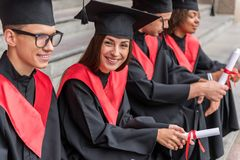 Excited students graduates on campus steps Royalty Free Stock Image