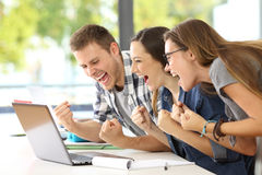 Excited students reading good news in a classroom. Side view of three excited students reading good news together on line in a laptop sitting in a desk in a royalty free stock photos