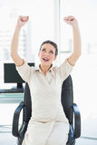 Excited stylish brunette businesswoman raising her arms Royalty Free Stock Photography