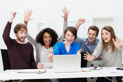 Excited successful business team cheering. Excited successful business team in front of laptop in the office Stock Photo