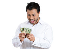 Excited successful young businessman holding the money that he earned Royalty Free Stock Photography