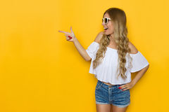 Excited Summer Girl Pointing. Ecstatic blond young woman in jeans shorts, white shirt and sunglasses holding hand on hip, looking away and pointing, Three Royalty Free Stock Photo