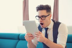 Excited surprised man watching tablet royalty free stock image