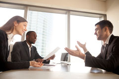 Excited surprised multi-ethnic recruiters listening to businessm Stock Photography