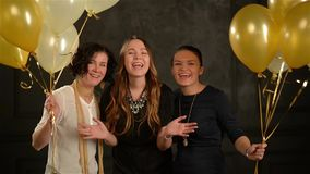 Excited Surprised Women Hiding among Balloons Having Fun during a Party. Closeup Portrait of Three Smiling Girls in the stock video