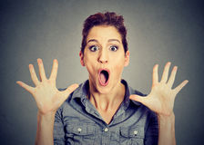 Excited surprised young woman screaming. Excited surprised woman screaming isolated on gray wall background Royalty Free Stock Image