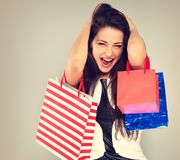 Excited surprising shouting woman with opened mouth in fashion white dress with shopping bags. Happy New Year Holidays sales stock images