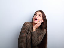Excited surprising young woman with open mouth looking up Stock Images