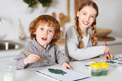 Excited talented siblings drawing some greens. Trees and bushes. Enthusiastic creative lovely children having fun and enjoying the process of painting while Stock Image