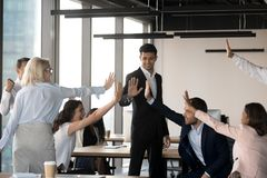 Excited team give high five celebrating shared success in office royalty free stock photos