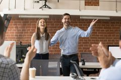 Excited team leader congratulating employee with promotion while. Excited company boss or team leader introducing new employee to colleagues in office welcoming royalty free stock image