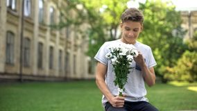 Excited teen boy with bouquet of flowers waiting for girlfriend, anticipation. Stock photo royalty free stock images