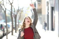 Excited teen celebrating good news in the street royalty free stock photos